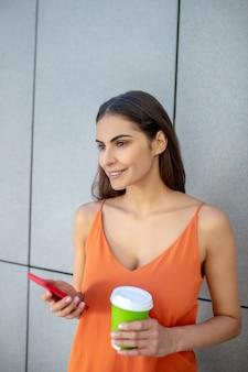 スマートフォンとコーヒーのカップを保持している黒髪のきれいな女性