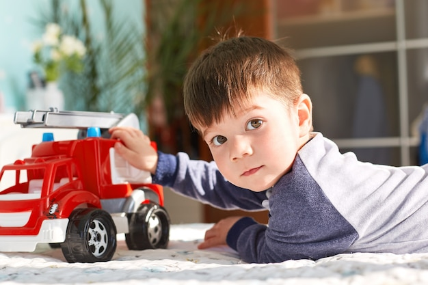 Dark haired small kid plays with toy car in bedroom