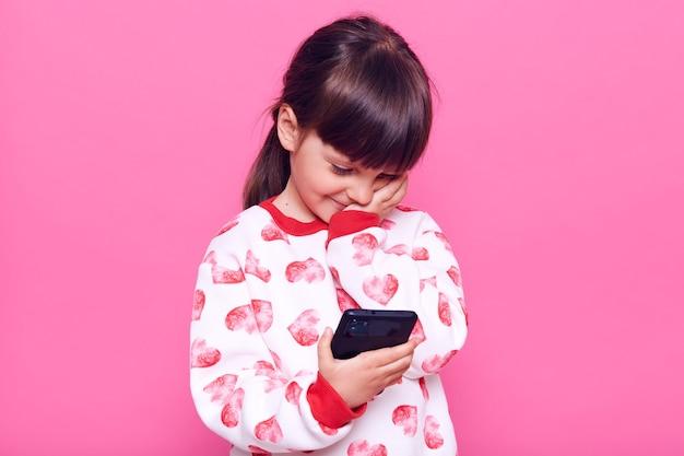 Темноволосая маленькая дошкольница с темными волосами и косичкой держит в руках смартфон, глядя на его дисплей, касаясь ее лица и улыбки, позирует изолированно над розовой стеной.
