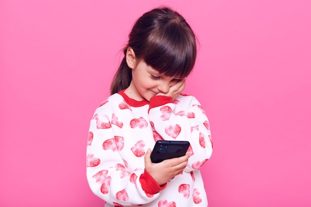Dark haired small preschooler girl with dark hair and pigtail holding smart phone in hands, looking at its display, touching her face and smile , posing isolated over pink wall.