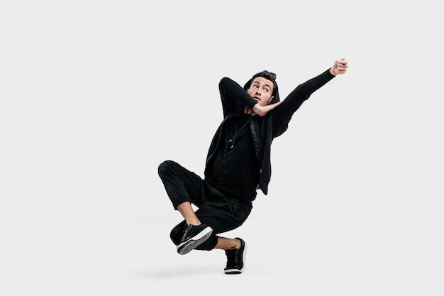 黒い服を着た黒髪のスタイリッシュなダンサーがストリートダンスの定型化された動きをします