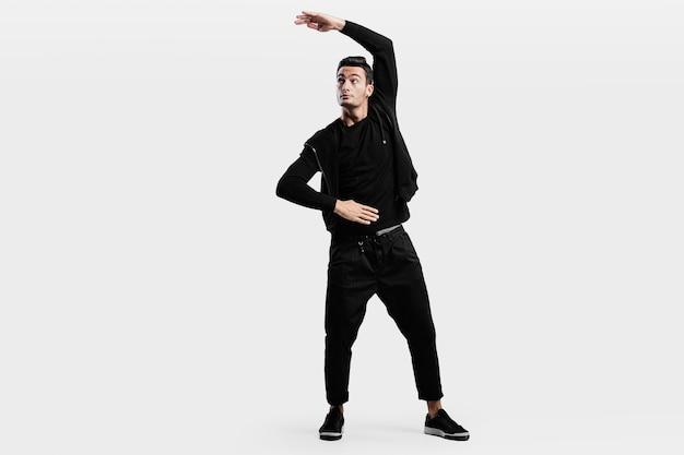 スタイリッシュな黒い服を着た黒髪のスタイリッシュなダンサーがストリートダンスを踊っています