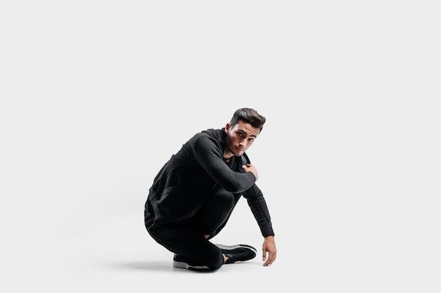 スタイリッシュな黒い服を着た黒髪のスタイリッシュなダンサーが床に座っています