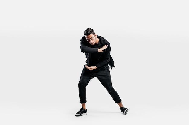 スタイリッシュな黒い服を着た黒髪のスタイリッシュな男がストリートダンスを踊っています