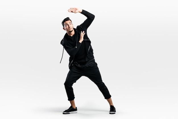 スタイリッシュな黒い服を着た黒髪のスタイリッシュな若い男がストリートダンスを踊っています
