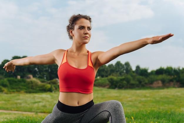 Темноволосая успешная привлекательная женщина проводит летнее утро на растяжке на открытом воздухе