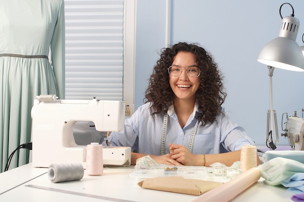Dark haired tailor girl with glasses smiles and looks at camera