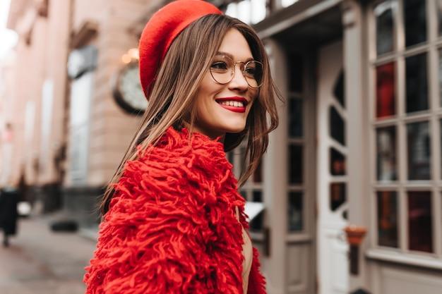 Donna abbronzata dai capelli scura con rossetto rosso in posa sulla strada. ritratto di giovane donna alla moda in cappotto e cappello lavorato a maglia rosso.