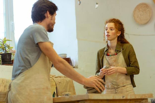 黒髪の先生。粘土を持ってプロの陶芸家に耳を傾ける長髪の女性に感動