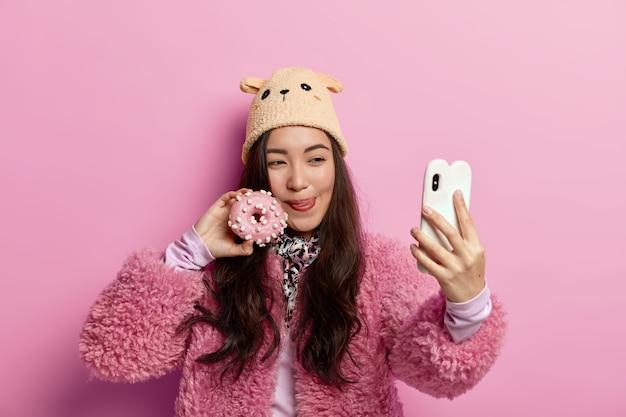 Adolescente dai capelli scuri si lecca le labbra, posa con una deliziosa ciambella glassata dolce, torna dal negozio di panetteria, si fa un selfie sul cellulare, si diverte