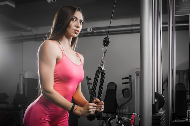 Dark-haired woman athlete in a tracksuit shakes hand-triceps biceps on a simulator in the gym.