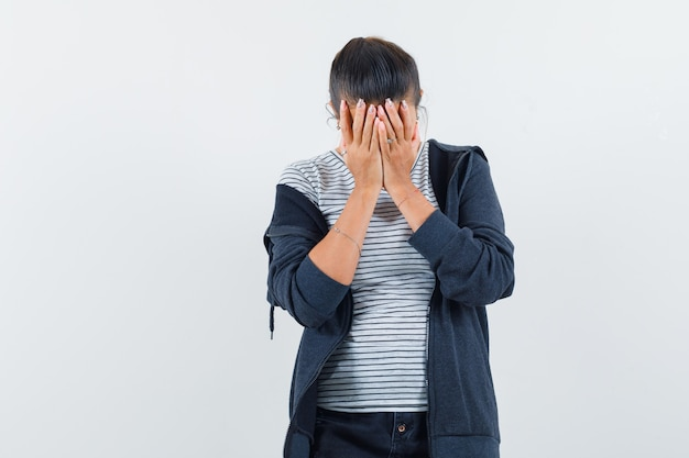 Dark-haired woman covering face with hands in shirt