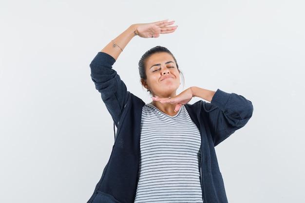 Donna dai capelli scuri che balla con le mani intorno alla testa in camicia