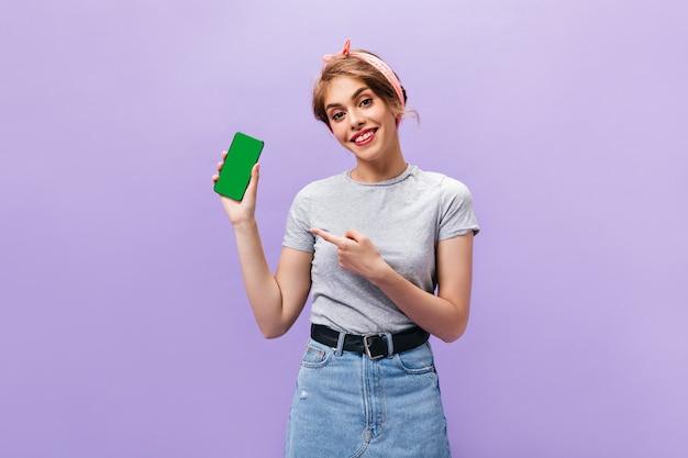 Темноволосая женщина демонстрирует черный смартфон. улыбается счастливая женщина в модной одежде, позирует на изолированном фоне.