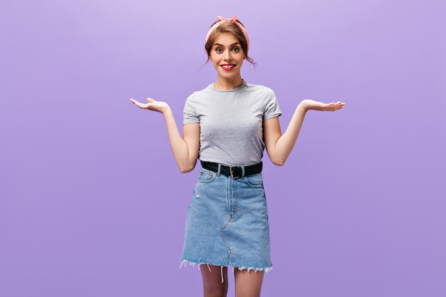 Dark haired woman in denim outfits shrugging. charming pretty girl with pink lips in grey t-shirt posing into camera on isolated background.
