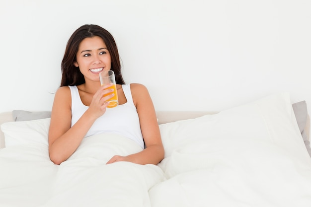 Dark-haired woman dinking orange juice sitting in bed looking at the ceiling