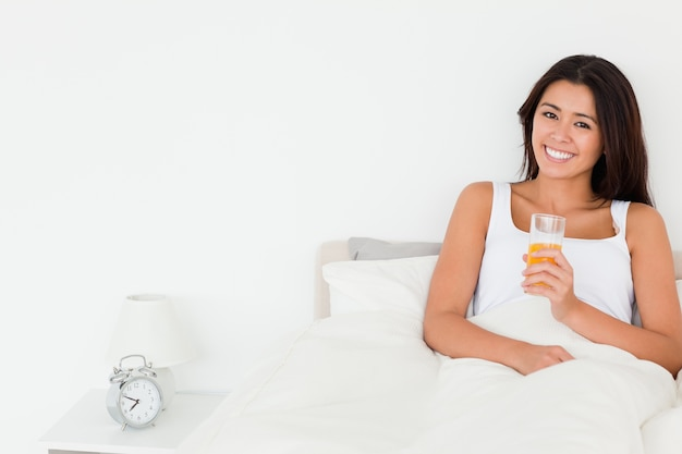 Dark-haired woman dinking orange juice sitting in bed looking into camera