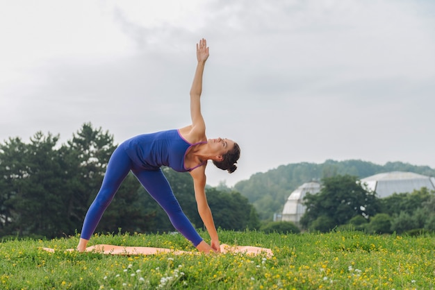 Темноволосая женщина наслаждается своим благополучием, стоя в стандартной позе йоги