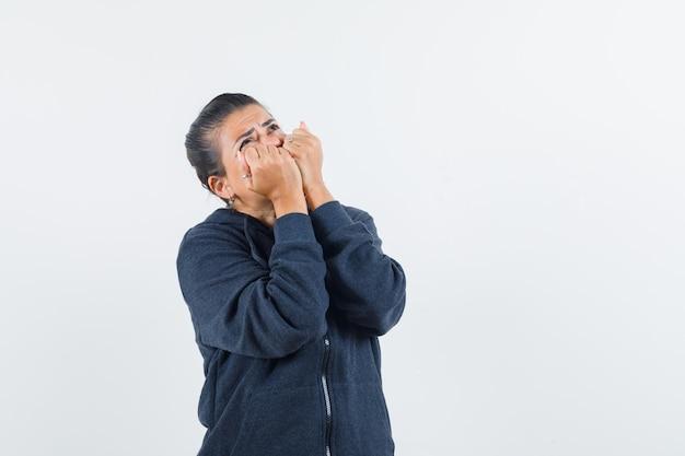 ジャケットを着て目をそらし、怖がっている間、彼女の口に拳を持っている黒髪の女性