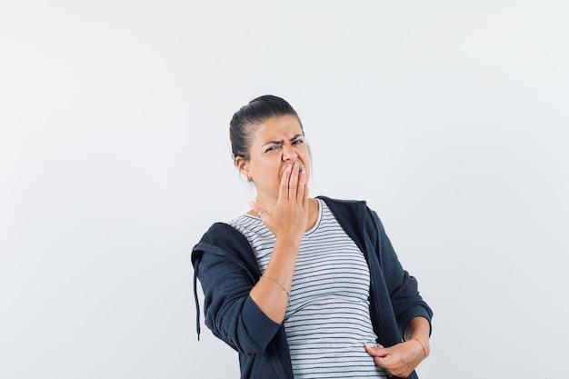 Donna dai capelli scuri che tiene la mano sulla bocca in camicia