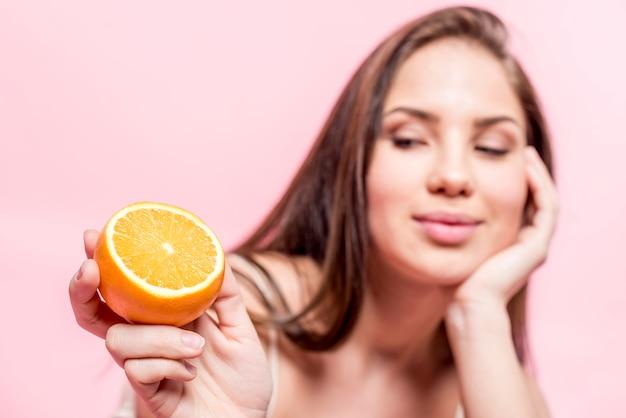 Dark haired woman holding sliced orange in hand