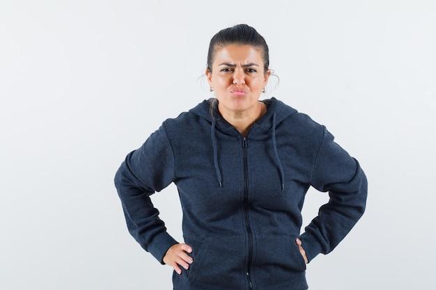 腰に手をつないで不満そうなジャケットを着た黒髪の女性
