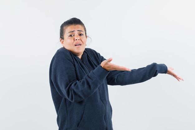 Темноволосая женщина в пиджаке показывает жест idk