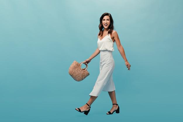 白い服を着た黒髪の女性は青い背景に移動し、わらのバッグを保持します。ライトロングドレスと黒の夏の靴の素敵な女性が微笑む。