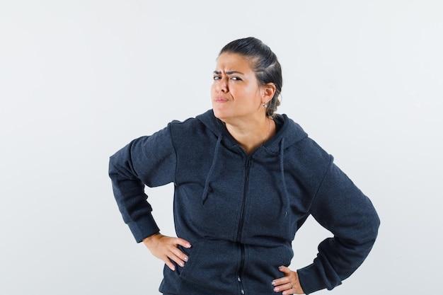 Donna dai capelli scuri in giacca tenendo le mani sulla vita mentre guarda attentamente la fotocamera e guardando concentrato