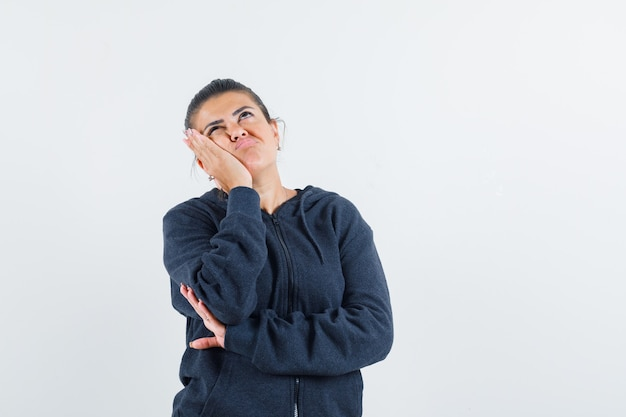 Donna dai capelli scuri in giacca appoggiata alla sua mano mentre pensa e sembra pensierosa