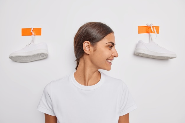 黒髪の女性は目をそらします笑顔は優しく着る靴を選びます漆喰のスニーカーで白い壁にカジュアルなtシャツのポーズを着て