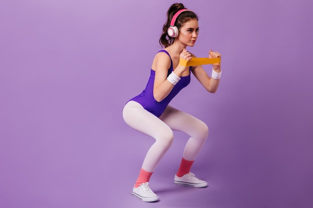 Dark-haired woman in purple tracksuit and white sneakers squatting with band for sports