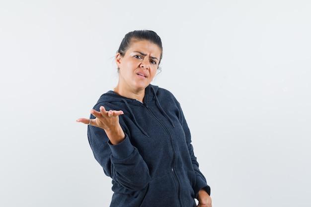 재킷에 공격적인 방식으로 손을 올리는 검은 머리 여자