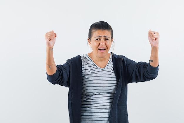 Donna dai capelli scuri che alza le braccia mentre mostra il suo potere in camicia Foto Gratuite