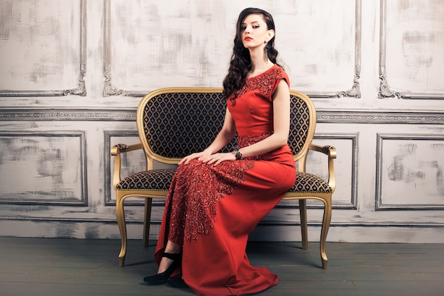 Dark haired woman in red evening gown seated on vintage chair
