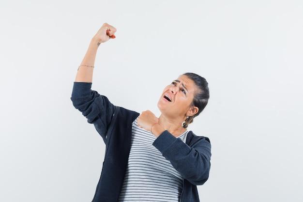シャツで腕の筋肉を見せている黒髪の女性