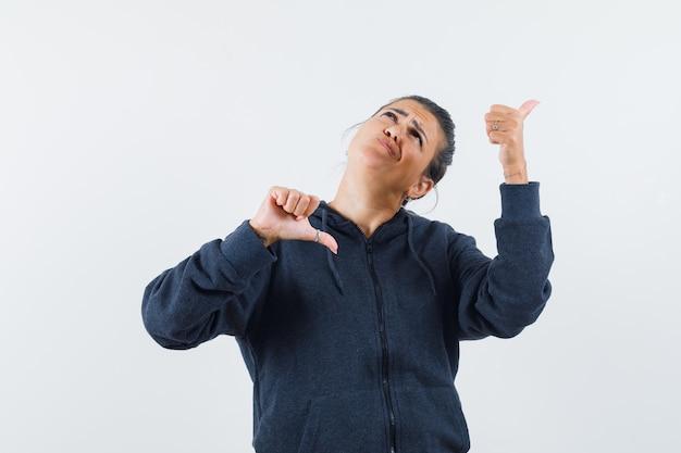 ジャケットで親指を上下に見せて困惑している黒髪の女性