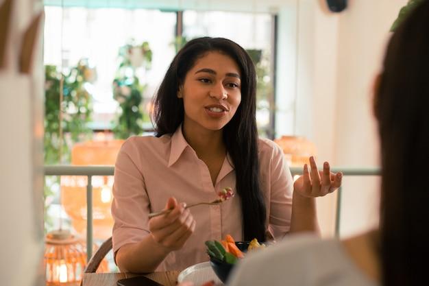 友人とカフェに座って食事をしながら身振りで示す黒髪の女性