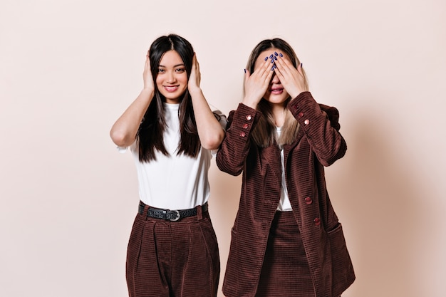 Dark-haired woman smiles and covers her ears, blonde woman in corduroy suit covers her eyes with her hands
