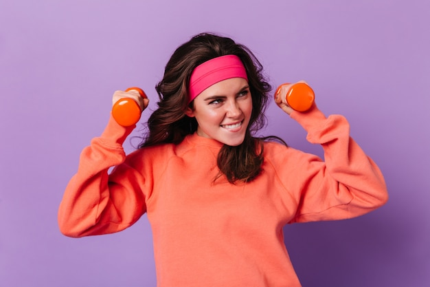 Dark-haired woman smiles and does exercises with dumbbells