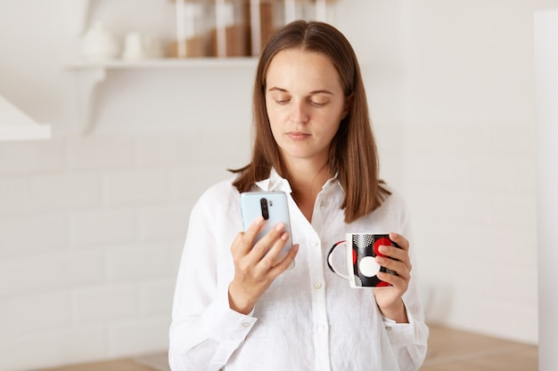 スマートフォンを持って立っている、ソーシャルネットワークでニュースを読んでいる、朝のキッチンでホットコーヒーやお茶を楽しんでいる、白いカジュアルなスタイルのシャツを着ている黒髪の女性。