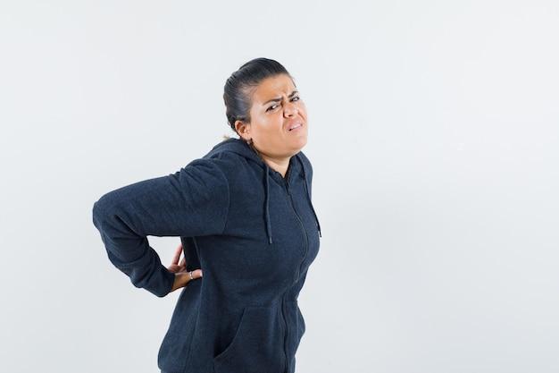Темноволосая женщина страдает от боли в шее в куртке и выглядит неудобно. передний план.