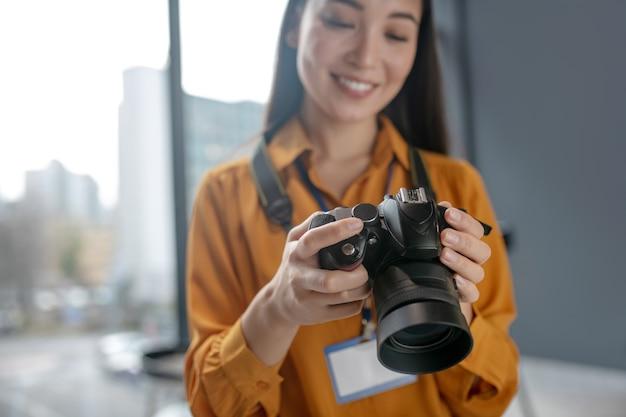 カメラで写真をチェックしながら笑っている黒髪の若いかわいいレポーター