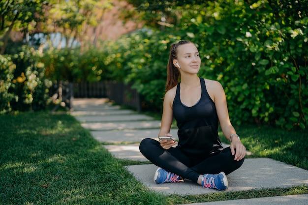 검은 머리 젊은 유럽 여성이 앉아있는 십자 다리는 만족스러운 표정으로 옆으로 보입니다. 스마트 폰은 활동적인 옷을 입고 심장 훈련 후 휴식을 취하고 운동화는 문자 메시지를 읽습니다.