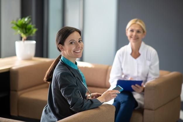 Темноволосая молодая женщина-стажер чувствует себя хорошо на работе, улыбаясь