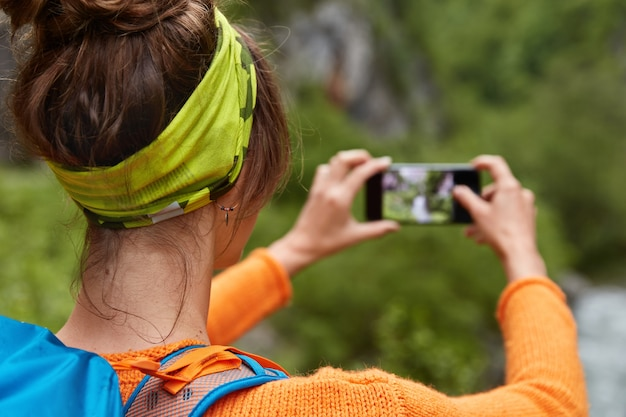 Dark haired young female stands back, wears green headband, carries rucksack, makes photo on smartphone device