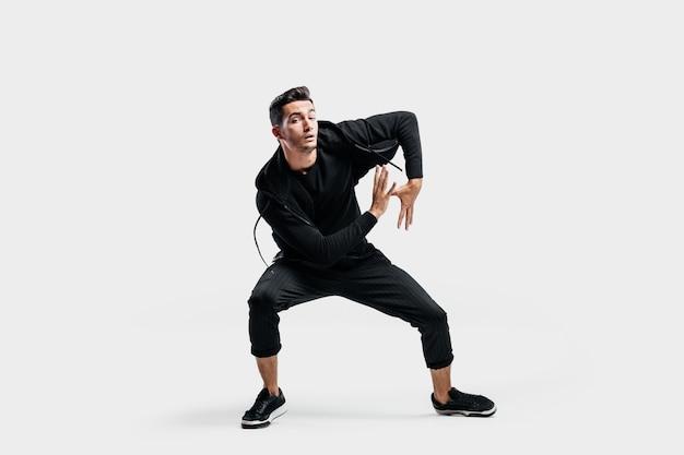 黒い服を着た黒髪の若い男がストリートダンスを踊っています