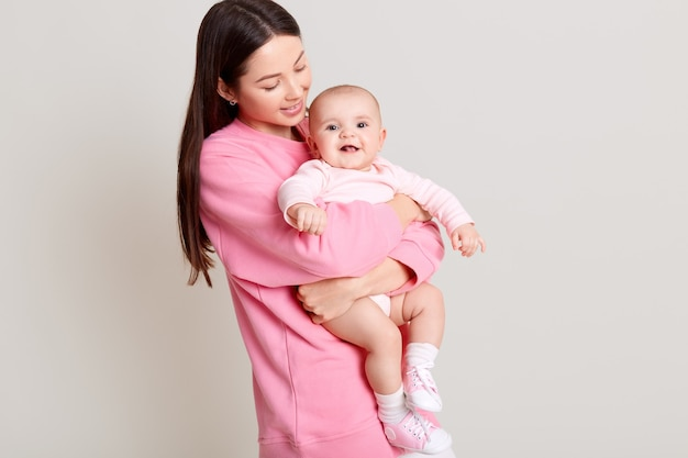Dark haired young mother hugging her daughter, baby smiling, mommy looking at infant, wearing casual pink sweater and white pants, isolated over light wall.