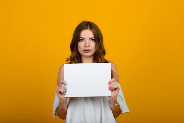 Темноволосая молодая женщина с улыбкой и большими удивленными глазами позирует на желтом фоне. макет на белой бумаге.