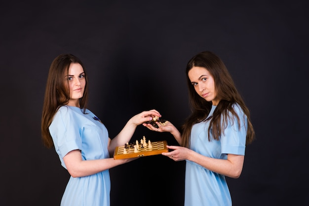 Dark-haired young women in a blue dress play chess on  yellow and black wall
